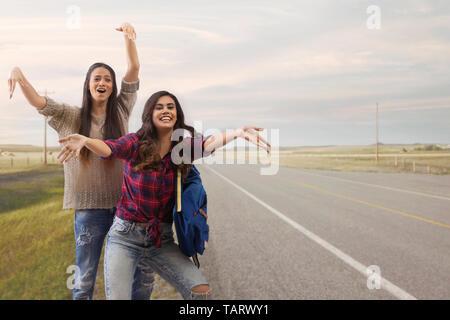 Deux femmes se tenant debout sur une route, des signes avec la main pour une levée Photo Stock