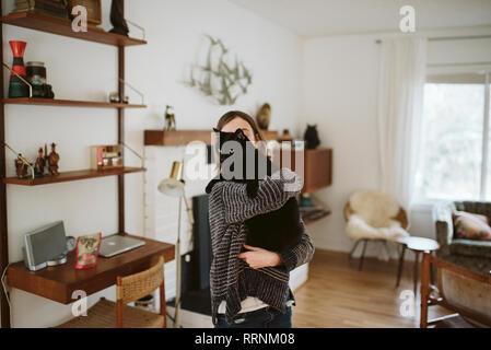 Girl holding chat noir dans la salle de séjour Photo Stock