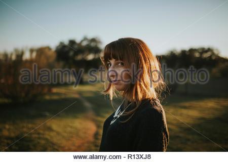 Portrait of a smiling woman standing dans un champ pendant le coucher du soleil Photo Stock