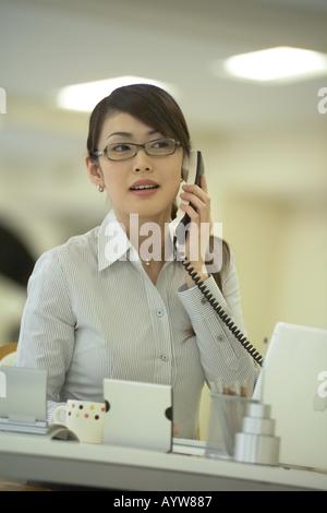 Femme parlant sur un téléphone dans le bureau Photo Stock