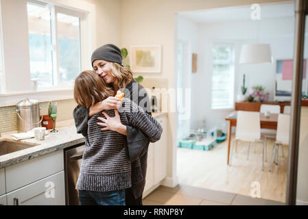 Affectueux mother and daughter hugging in kitchen Photo Stock