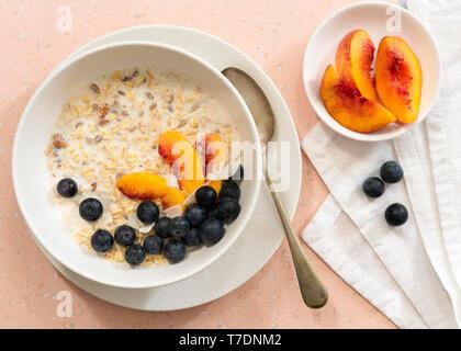 L'avoine, tranches de pêches, les bleuets et le lait dans un bol pour le petit déjeuner. Photo Stock