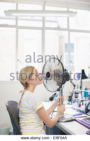 Smiling woman sitting in front of fan in office Photo Stock