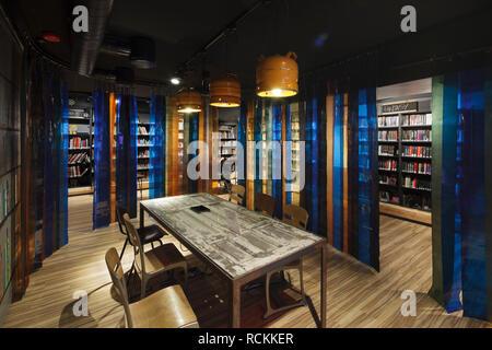 Salle d'étude en sous-sol salle de lecture avec parquet en bois et acrylique bleu et orange divisant les séquences. Bibliothèque Deichman Toyen, Oslo, Norvège. Architecte: Photo Stock