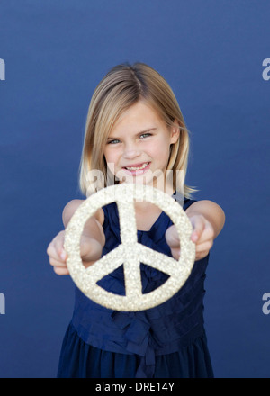 Portrait of young girl holding up peace sign Photo Stock