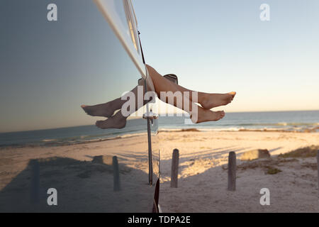 La section basse de Caucasian woman relaxing with feet up dans un camping-car at beach Photo Stock