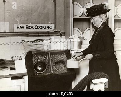 Démonstration de cuisine Boîte de foin à l'exposition de conservation des aliments, Institut d'hygiène (qui a ouvert ses portes le 28 janvier 1918). Un haybox, paille fort, Cuisinière Fireless, l'isolement d'une cuisinière, d'un étonnant four ou conservé à la chaleur de cuisson est une cuisinière qui utilise la chaleur de la cuisson des aliments pour compléter le processus de cuisson. Articles alimentaires pour être cuites sont chauffés à point d'ébullition, puis isolé. Photo Stock