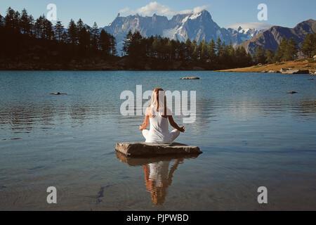 La femme trouve la paix en lac de montagne. Position de Yoga Photo Stock