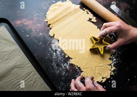 High angle portrait de personne couper des cookies en forme d'étoile à partir de la pâte à biscuit. Photo Stock