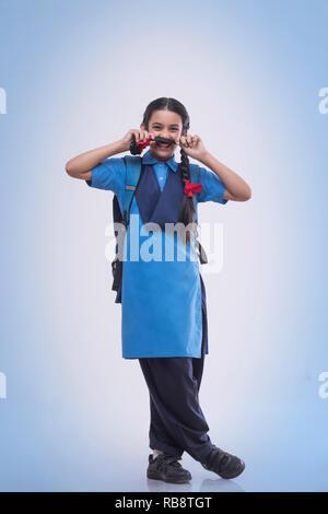 Fille de l'école ludique faisant une moustache avec ses cheveux sur un fond bleu Photo Stock