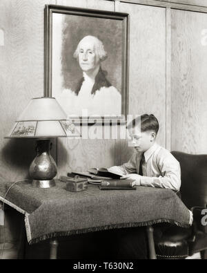 1930 garçon STUDIEUX FONT LEURS DEVOIRS ASSIS À LA TABLE DE LECTURE SOUS PORTRAIT DE GEORGE WASHINGTON - s8901 HAR001 HARS STUDIEUX JEUNES NOIR ET BLANC LAMPE DE TABLE Origine ethnique Caucasienne HAR001 old fashioned Photo Stock