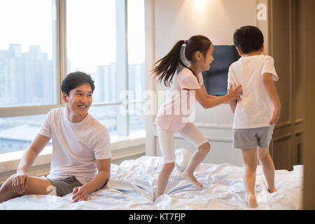 Cheerful young family having fun sur un lit Photo Stock