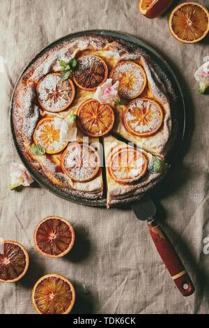 Gâteau au fromage fait maison découpées avec les oranges sanguines de Sicile, décoré par des fleurs comestibles, les feuilles de menthe, le sucre en poudre a servi dans la plaque avec les oranges coupées abo Photo Stock