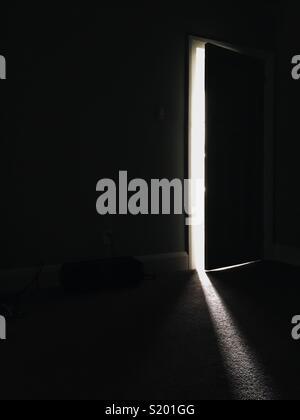 La lumière à travers une porte ouverte la nuit Photo Stock