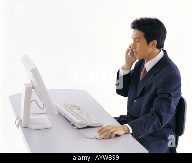 Office worker talking on a cell phone in front of computer Photo Stock