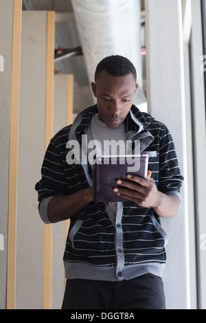 Dix-huit ans college student à l'aide d'un ipad dans un couloir. Photo Stock