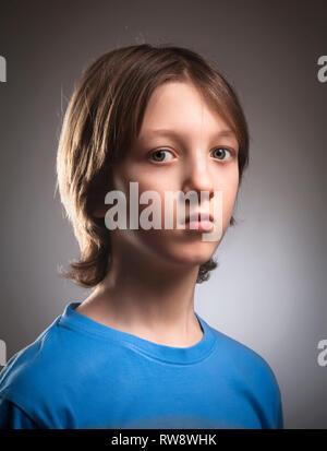 Portrait d'un garçon aux cheveux blonds en haut bleu. Photo Stock