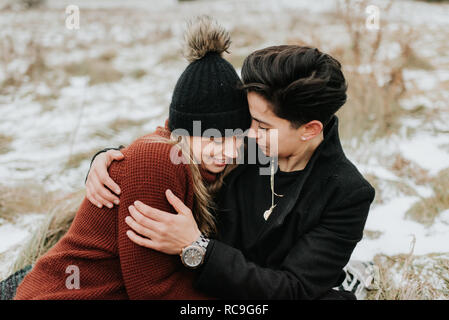 Couple assis sur une couverture sur un sol gelé, Georgetown, Canada Photo Stock