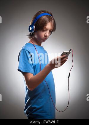 Garçon avec les cheveux bruns à écouter de la musique dans le casque. Photo Stock