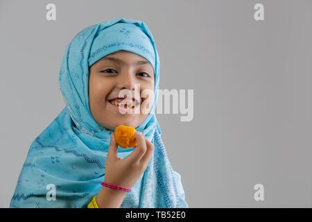 Jeune musulmane portant le hijab de sourire et de manger des douceurs Photo Stock