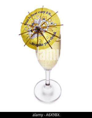 Un cocktail parapluie dans un verre de Champagne montrant comment il est facile de placer quelque chose dans votre Photo Stock
