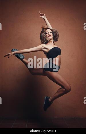 Belle gymnaste sauts. La danse moderne et de l'aérobique Photo Stock