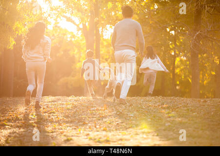 Young family playing in autumn woods Photo Stock