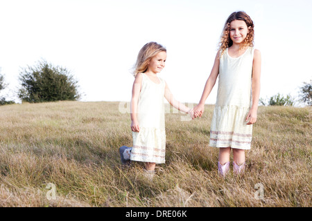 Soeurs en robes standing in field Photo Stock