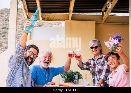 Happy Family enjoying party ensemble sur la terrasse. Groupe de 4 personnes souriantes célébrer avec du vin rouge et de l'eau Photo Stock