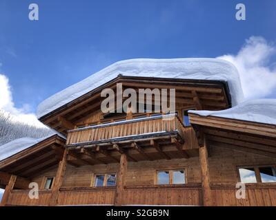 La neige profonde couvre un toit dans les Alpes autrichiennes sur lumineuse, ensoleillée mais froide journée d'hiver. Photo Stock