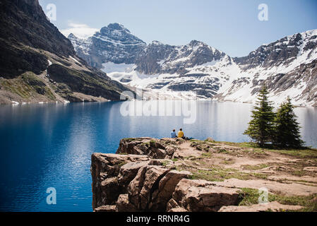 Couple tranquille, ensoleillée falaise donnant sur le lac et les montagnes, le parc Yoho, Colombie-Britannique, Canada Photo Stock