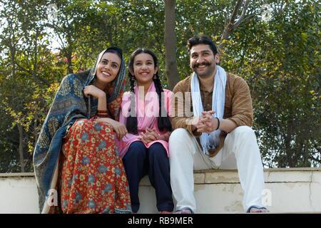 Happy Village couple avec leur fille, assis sur les marches à l'extérieur. Photo Stock