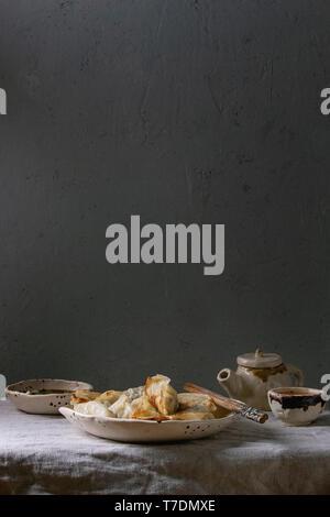 Les Gyozas frits boulettes asiatiques potstickers dans une plaque en céramique blanc servi avec bol de sauce de soja, l'oignon sur la théière , tapis de table. Dîner asiatique Photo Stock