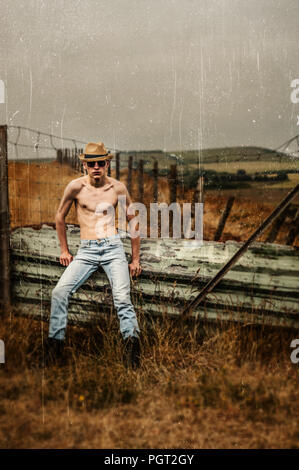 Young man wearing straw hat standing dans les champs Photo Stock