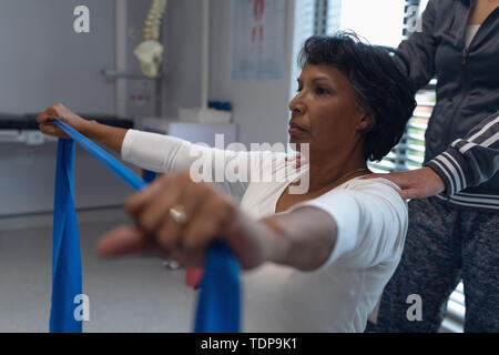 Vue latérale d'une femme de race blanche donnant un physiothérapeute thérapie physique avec bande de résistance à mixed race female patient dans l'hôpital Photo Stock