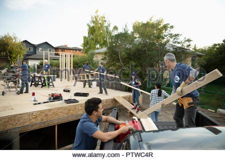 Les bénévoles du déchargement plancher bois, aider à favoriser l'house Photo Stock