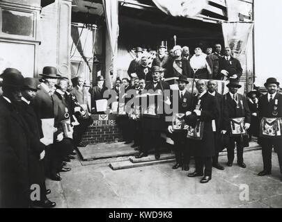 Arthur Alfonso Schomburg dans un groupe de maçons et Odd Fellows, Avril 1, 1922. Il est debout devant un mur Photo Stock