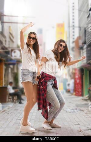 Deux jeunes femmes dansant sur l'écoute de la musique de rue Photo Stock