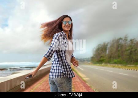 Jeune femme marche sur une route holding a mobile phone Photo Stock