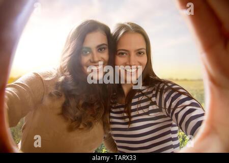 Portrait de deux femmes vu dans l'écart de leurs mains tenues ensemble Photo Stock