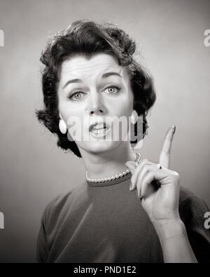 Années 1950 Années 1960 BRUNETTE WOMAN PEARL STRAND EARRINGS DOIGT EN PARLANT DE PARLER À LA CONFÉRENCE DE L'APPAREIL PHOTO À ENSEIGNER À NAG - g4859 HAR001 EXPRESSIONS HARS B&W CONFÉRENCE CONCERNÉS DANS LES YEUX DE LA TÊTE ET DES ÉPAULES BRUNE STYLES LANCINANTE JUSQU'AU FOYER DE L'AUTORITÉ D'ENSEIGNER LES MÉTIERS DE FAUX porte-parole auto-assuré élégant STRAND BIJOUX FASHIONS MID-ADULT MID-ADULT WOMAN NAG NOIR ET BLANC DE L'ORIGINE ETHNIQUE CAUCASIENNE HAR EXPRESSIF001 old fashioned Photo Stock