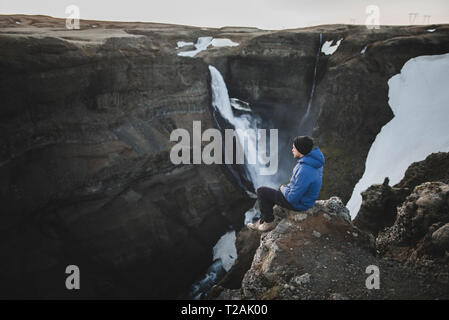 Randonneur assis sur falaise par Haifoss cascade en Islande Photo Stock