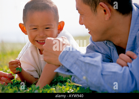 Père couché dans la prairie avec son fils Photo Stock