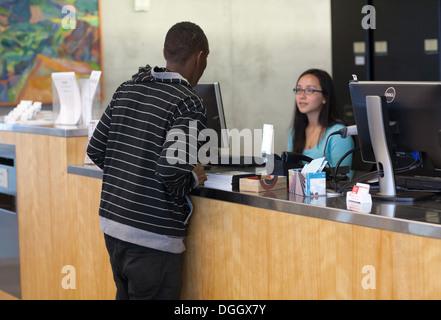 African teenage étudiant demande bibliothécaire de référence une question. Photo Stock