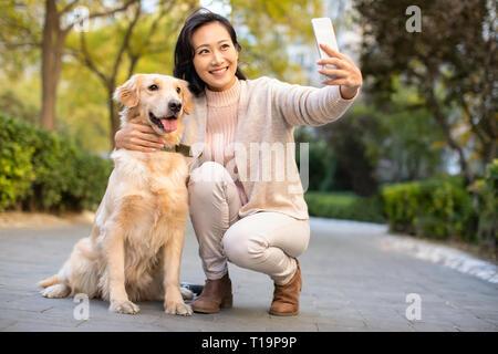 Heureux de prendre une jeune femme avec son chien selfies Photo Stock