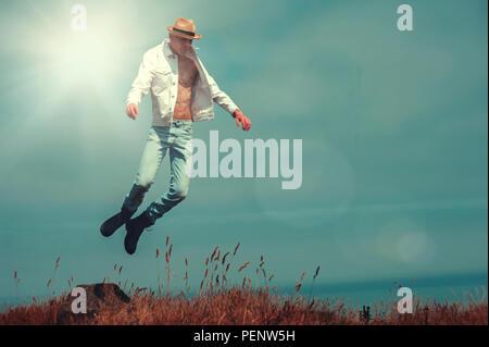 Jeune homme volant dans des champs sur falaise Photo Stock
