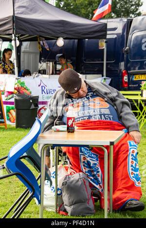 Harris est juste avec la masse des hommes âgés ayant figure affalé dans président endormi avec cola Bouteille sur table Photo Stock