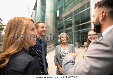 Smiling business people talking sur trottoir urbain Photo Stock