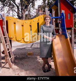 Middle-aged woman leaning on glisse à l'aire de jeux Photo Stock