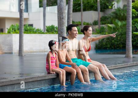 Jeune famille chinoise assis côte à côte à la piscine Photo Stock